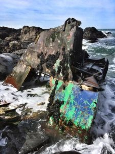 Image of boat which has hit rocks and broken apart