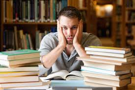 Male with head in hands, looking out over stacks of books and notebooks--but not reading them