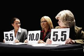 Three judges, each holding up a scorecard. Two are 5.5; third is 10.0