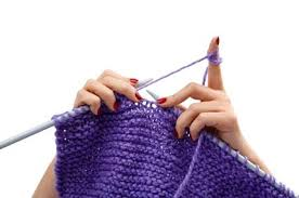 Two hands, knitting with bright purple yarn
