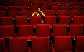 Person alone in otherwise empty movie theatre