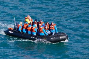 Lifeboat full of people, all wearing safety vests