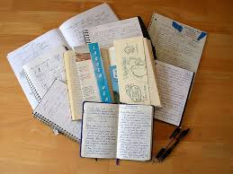 Pile of notebooks and resources, and few pens