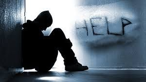 """Student leaning against wall, distressed-looking, word """"HELP"""" on wall"""