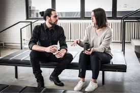 Two adults sitting on bench, talking