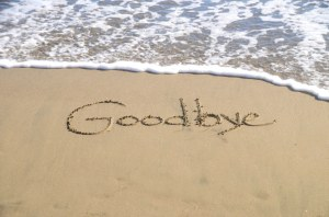 """Sand and wave approaching; in the sand, someone has written """"Goodbye"""""""