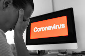 "Man, head in hand, with computer screen behind him that says ""Coronavirus"""