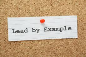"Corkboard with message pinned to it; says ""Lead by Example"""